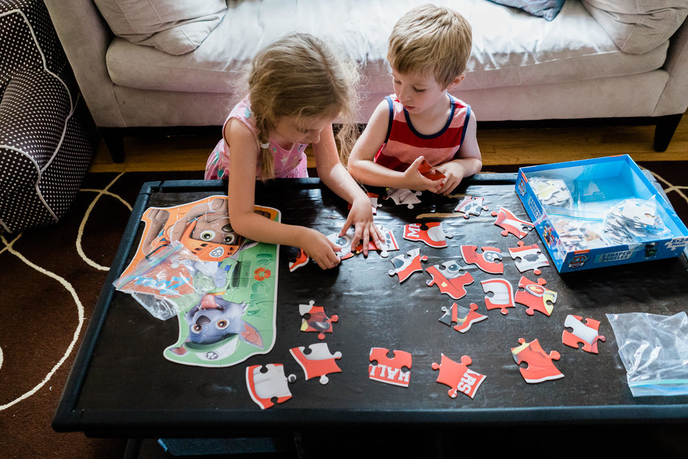 A boy and girl do a puzzle at the coffee table.