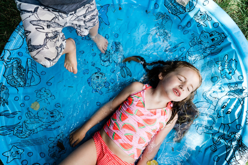 A little girl lies down in a wading pool.