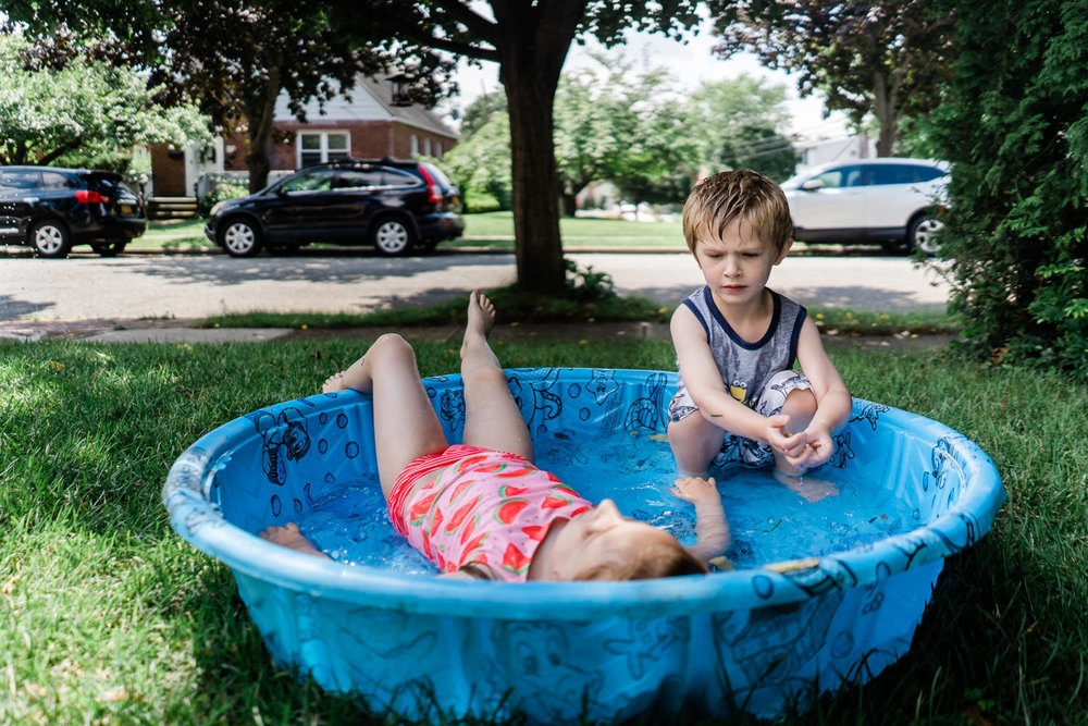 Two kids play in a wading pool on their front lawn.