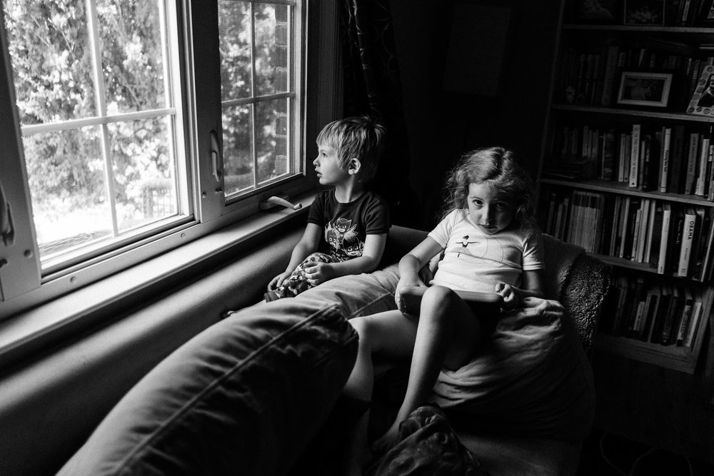 Two kids read on the couch.
