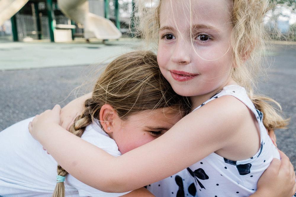 Two little girls embrace.