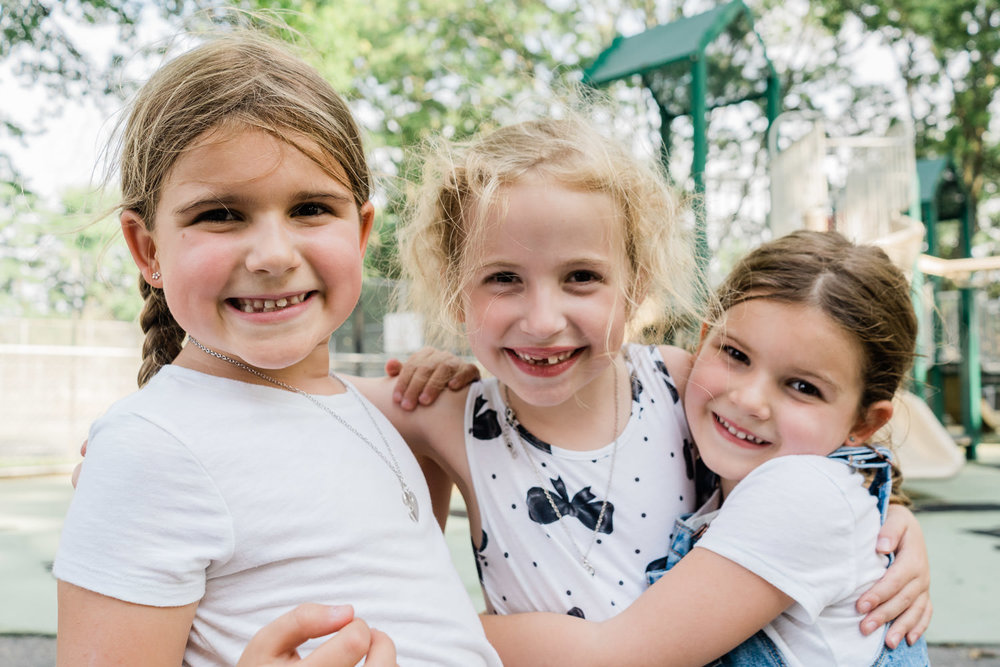 Three little girls smile at the camera.