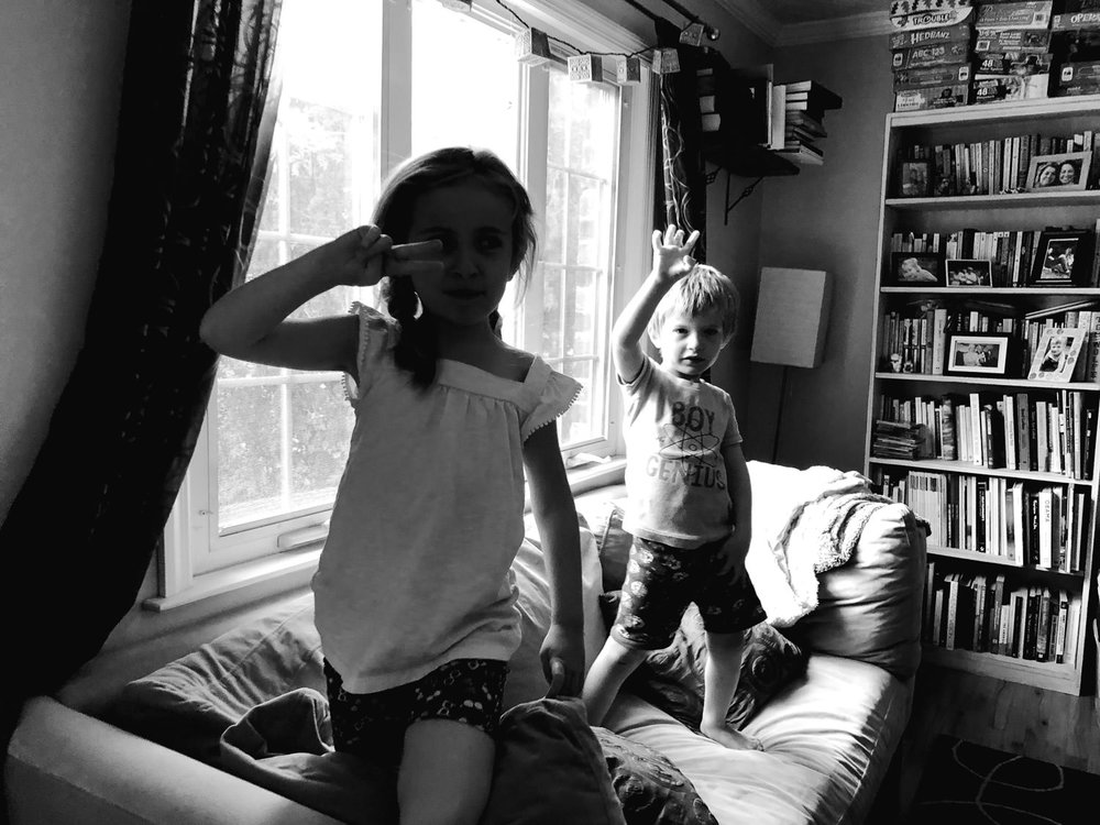 Two children jump on a couch.