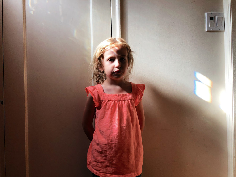 A little girl stands near a patch of light in a hallway.