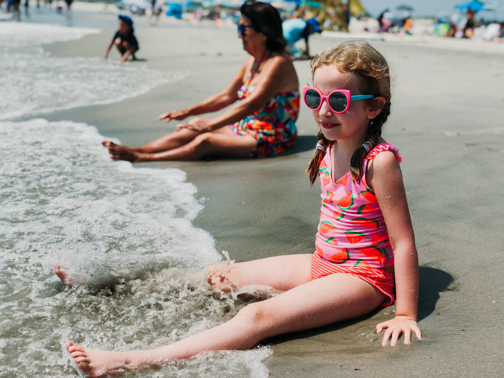 A little girl sits in the waves at Lido Beach.