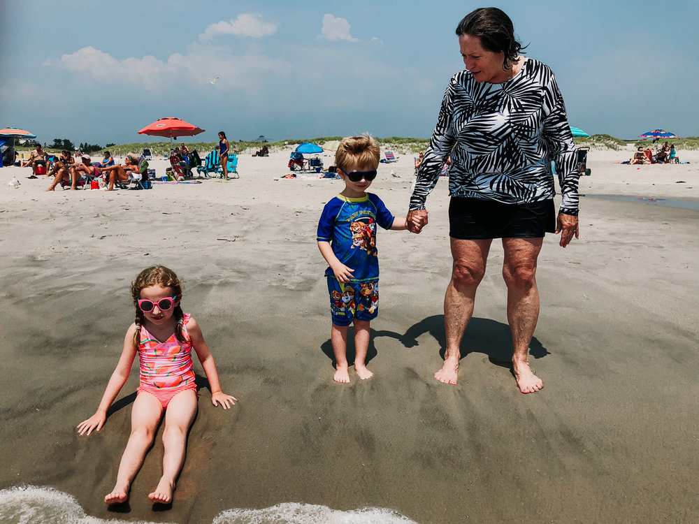 A family stands on the shore at Lido Beach.