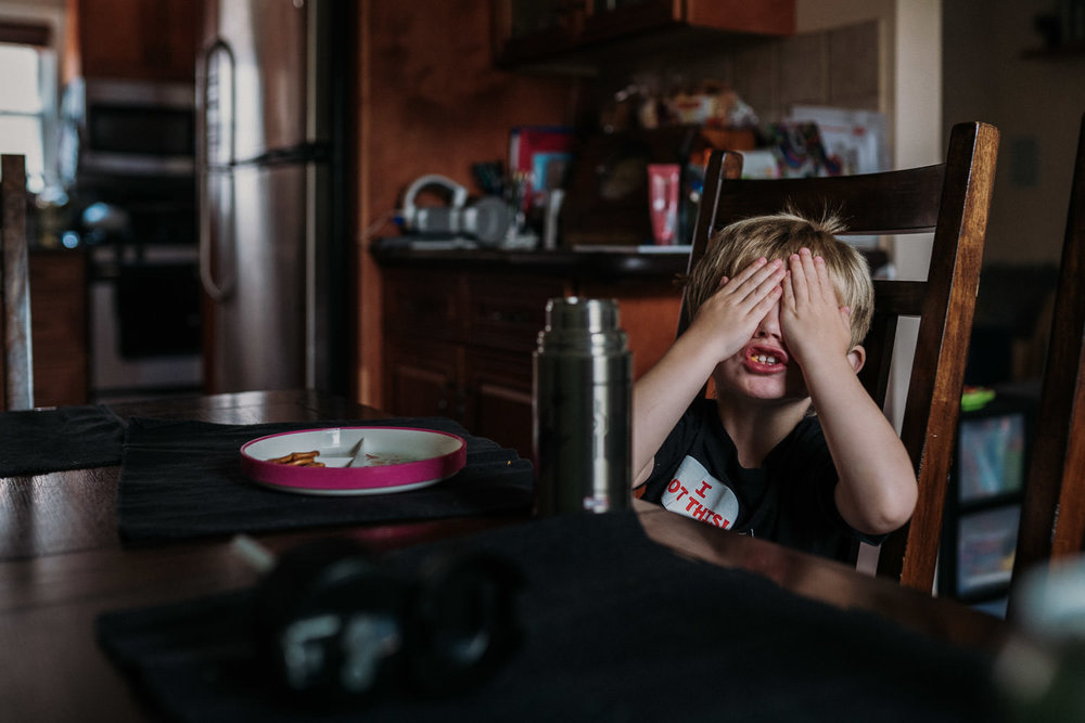 A little boy sits at the kitchen table and covers his eyes.