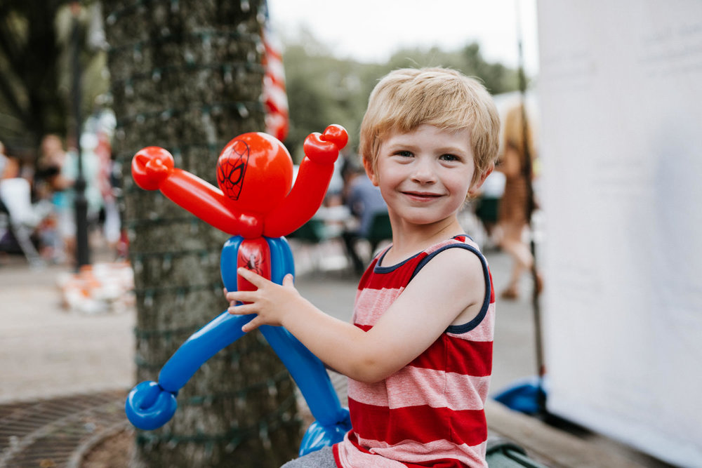A little boy holds a SpiderMan balloon at 7th Street in Garden City.