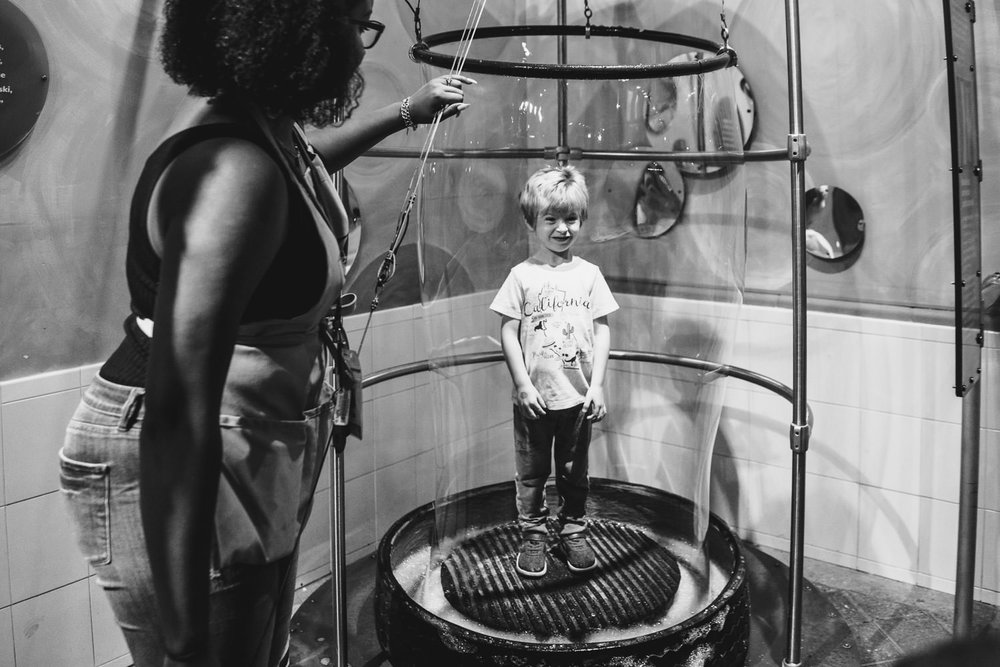 A little boy stands in a bubble at the Long Island Children's Museum.