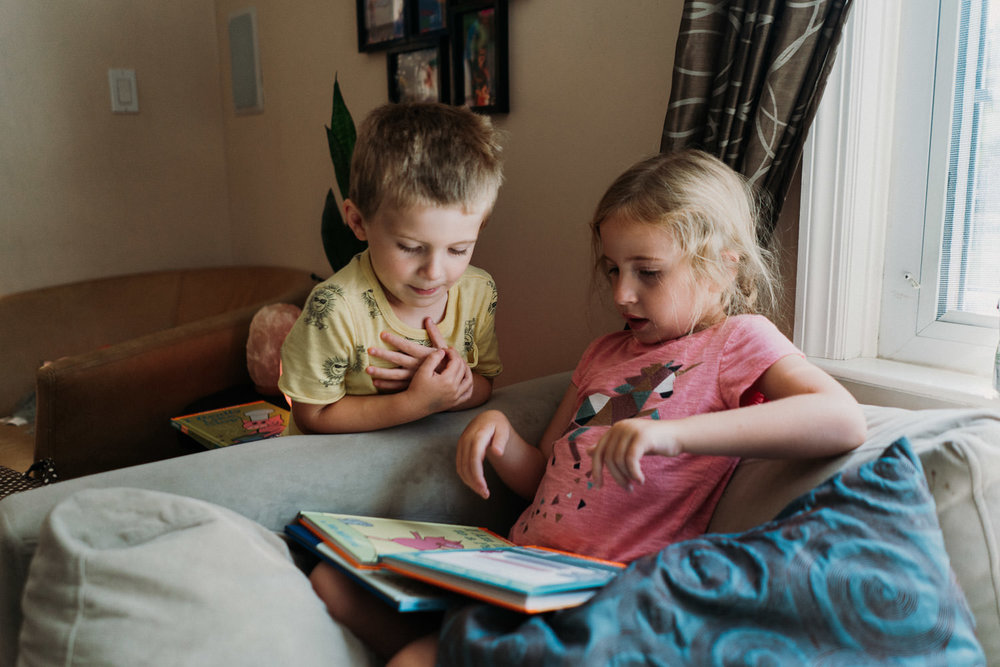 Kids read books on the couch.