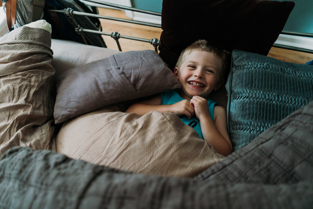 A little boy covered in pillows lies on his parents' bed.