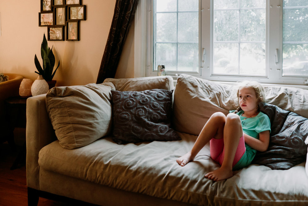 A little girl sits on a couch.
