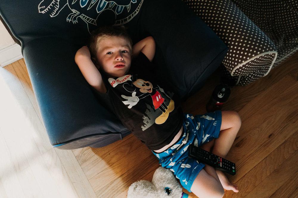 A little boy lies on the floor.