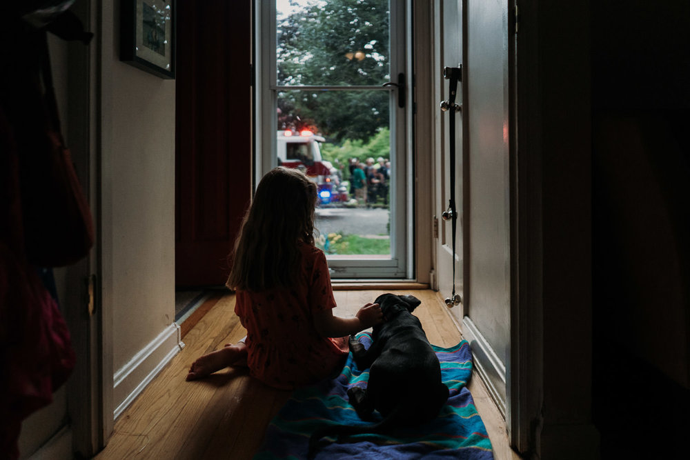 A girl and her dog look out the front door.