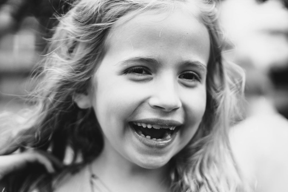 A little girl missing her two front teeth smiles