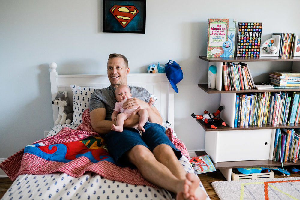 A father reclines on a bed with his baby girl.