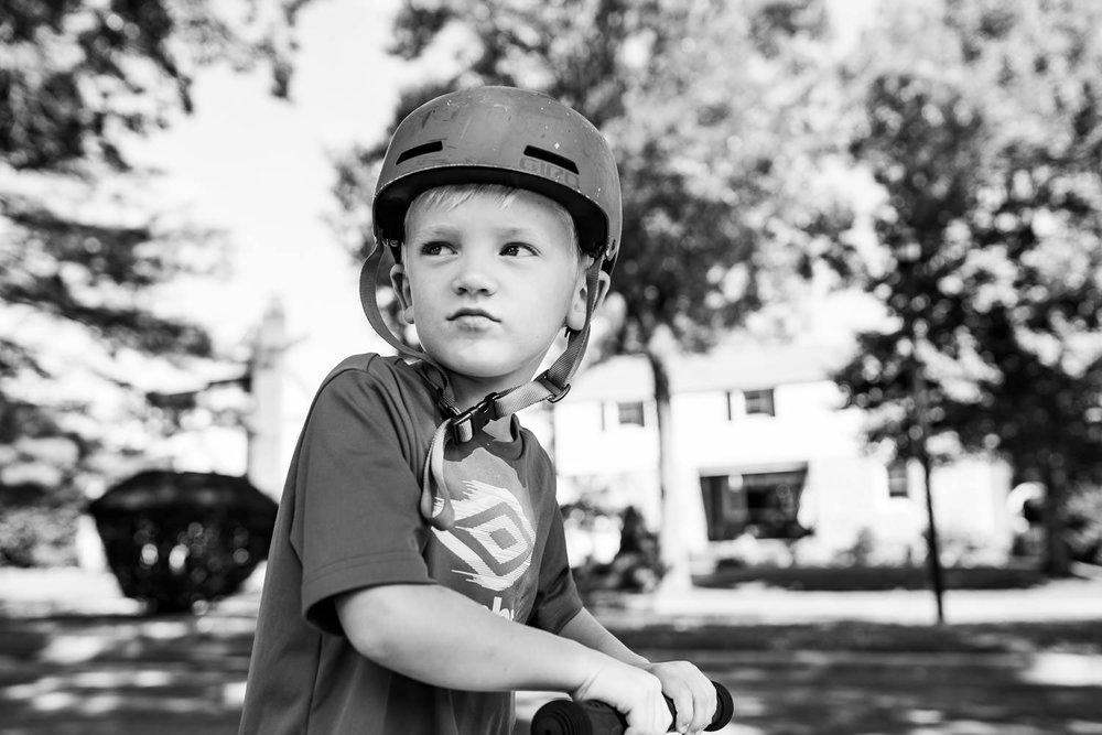 A little boy wears a bike helmet.