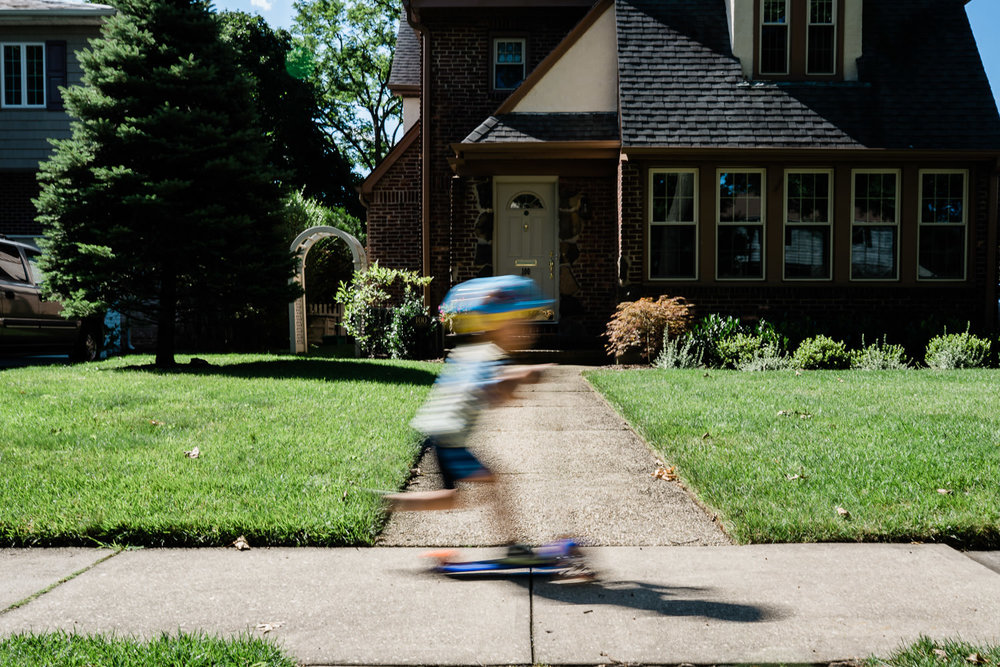 A little boy rides his scooter past his house.