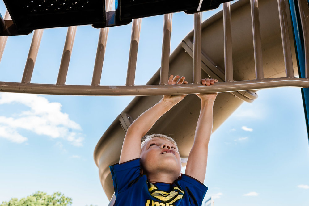 A little boy hangs from a playground structure.