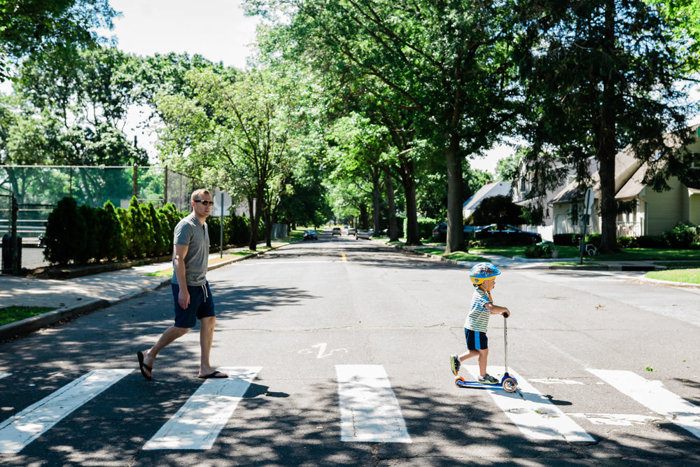 A father crosses the street with his son on a scooter.