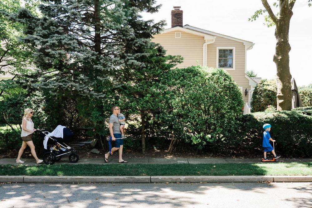 A family walks down a suburban street.