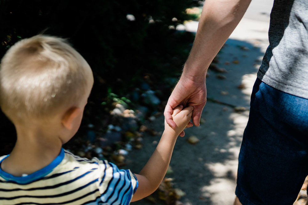A father holds his toddler son's hand.