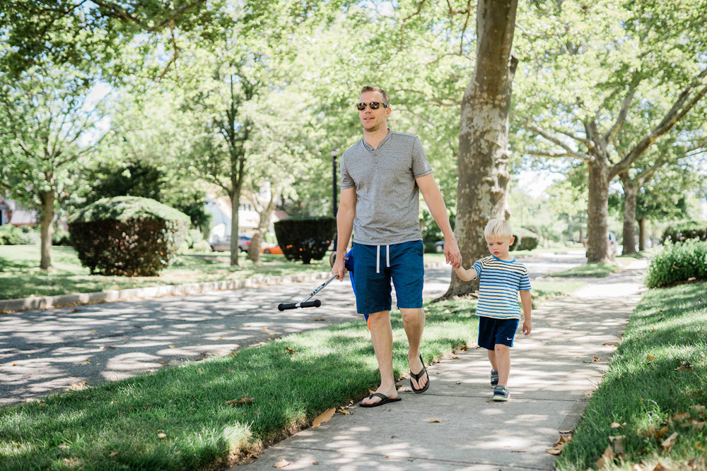 A father holds his son's hand as they walk home.