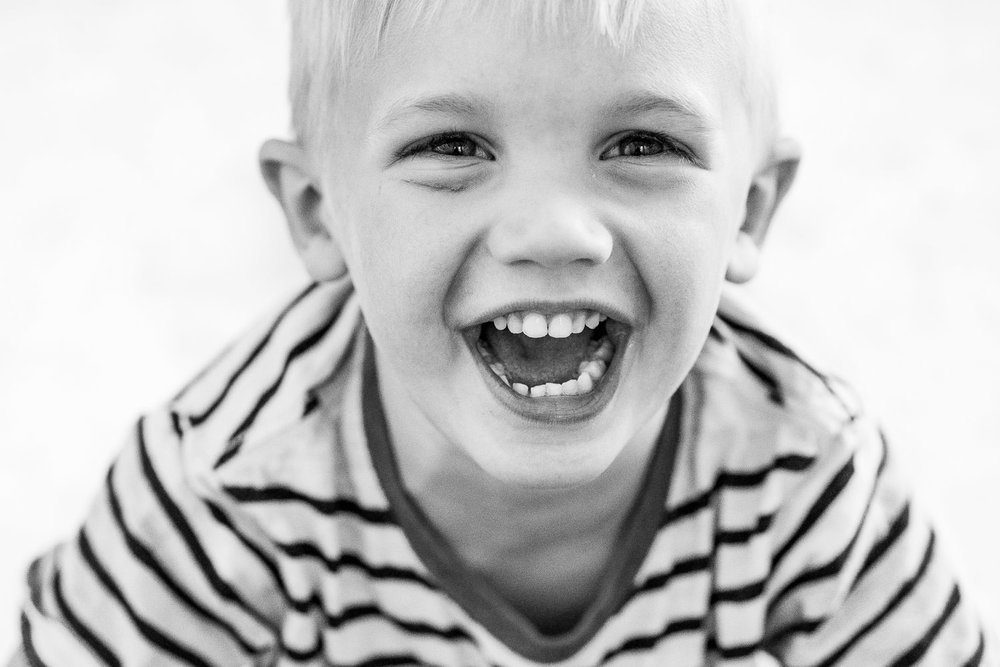 A black and white portrait of a little boy laughing.