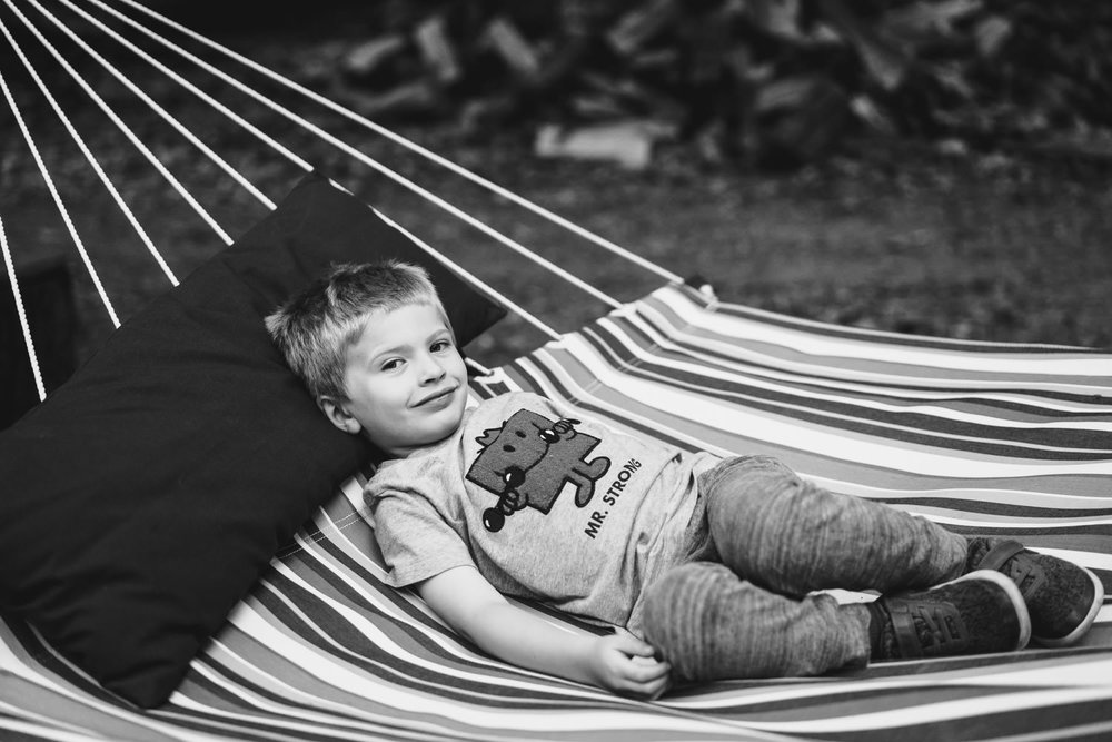A little boy lies in the hammock.