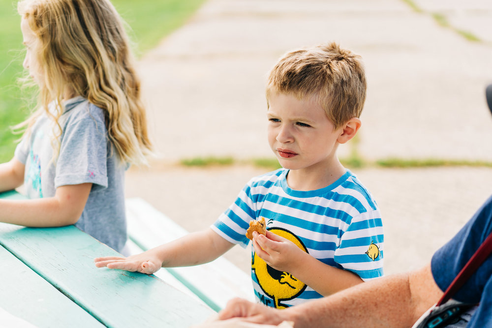 A little boy sits at a picnic table and enjoys a cookie.