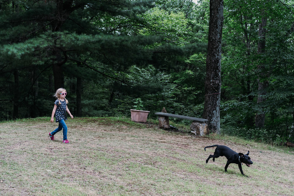 A little girl chases her dog across the lawn.
