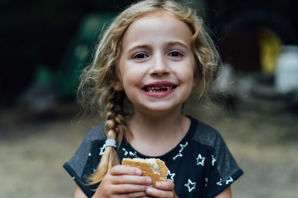A little girl smiles with her s'more.