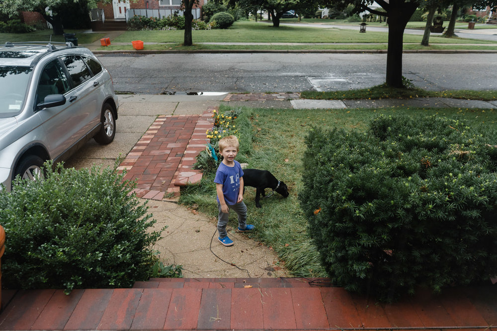 A little boy stands next to his dog on his front walkway.