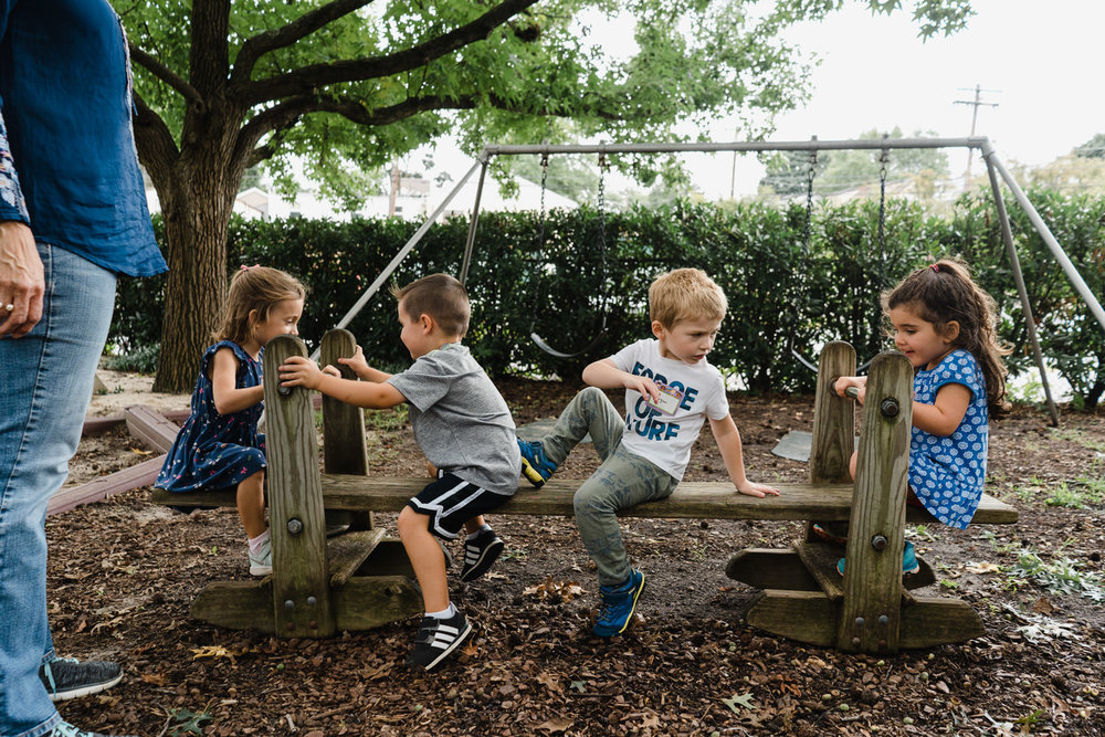 Preschoolers play on a see saw.