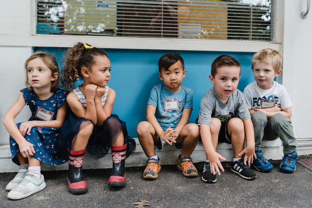 Preschoolers sit outside their classroom.