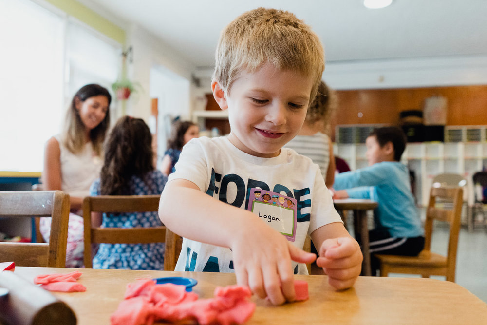 A little boy plays with play doh in his classroom.