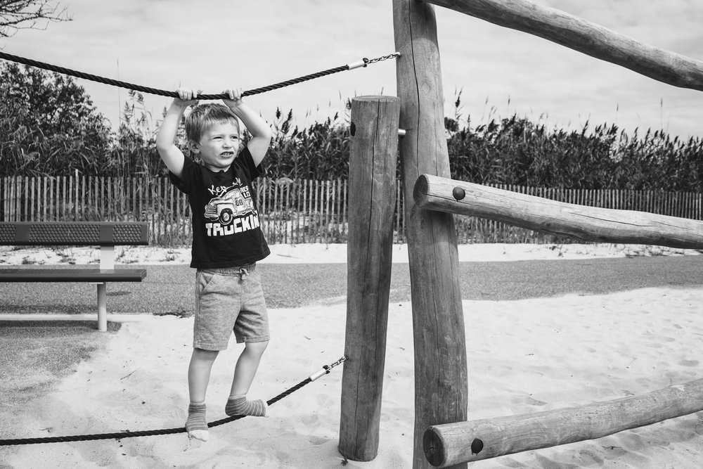 A little boy plays on a playground at Captree State Park.