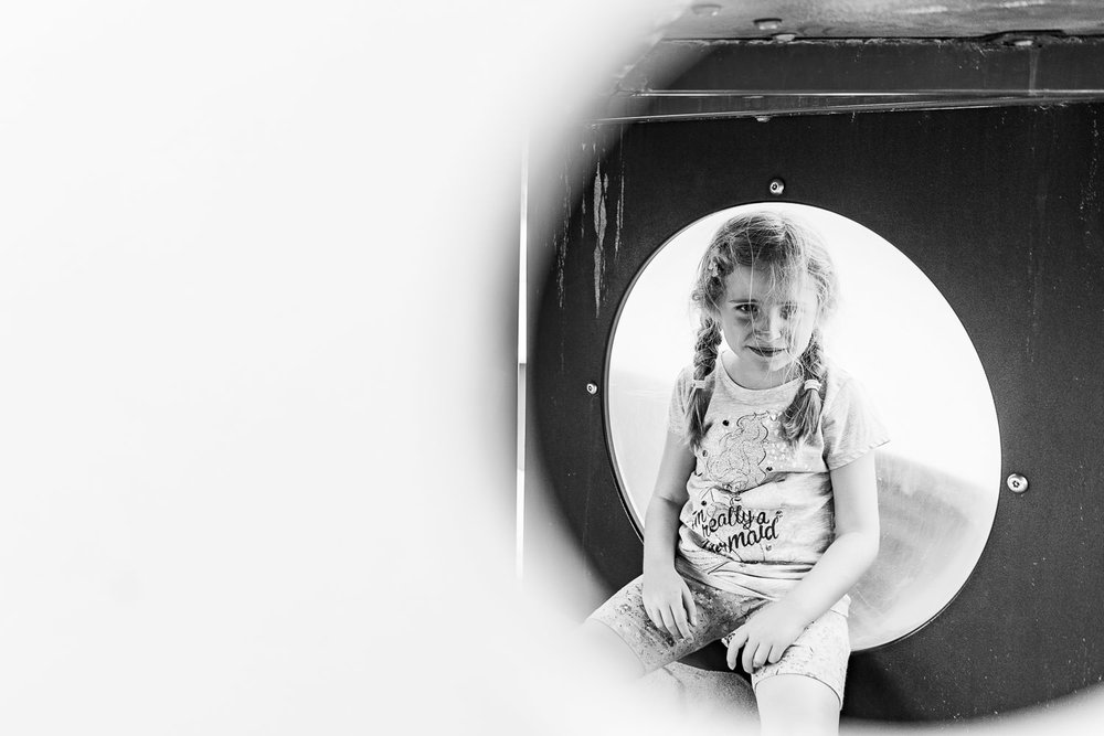 A little girl sits inside a play structure.