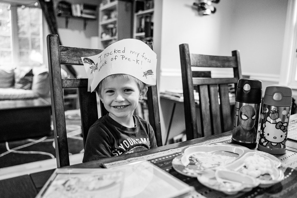 A little boy wears a homemade hat celebrating his first week in