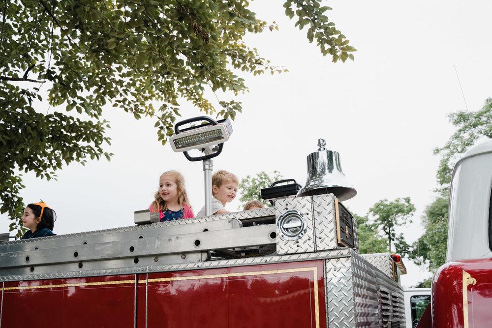 Kids climb on top of a fire truck.