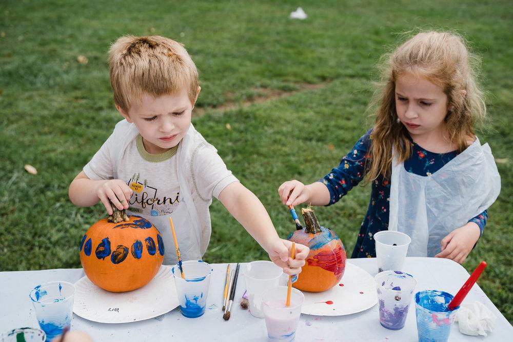 Two children paint pumpkins at a fair at Sands Point.