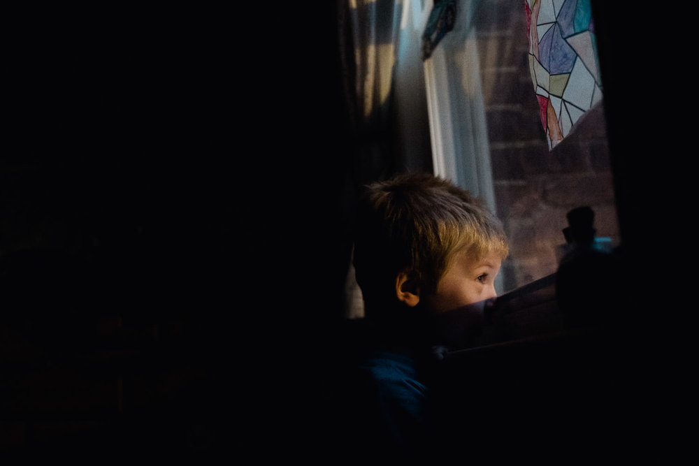 A boy looks out his bedroom window.