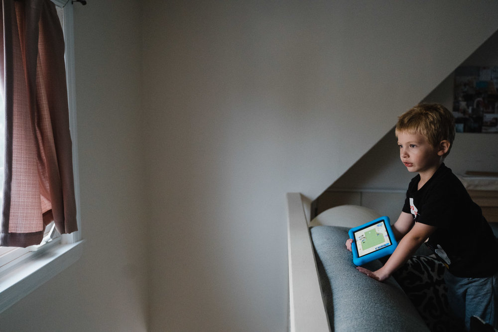 A little boy stands on a couch holding a tablet.