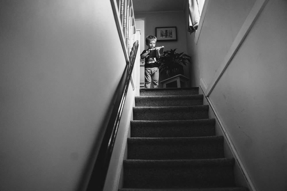 A little boy stands at the top of a staircase.