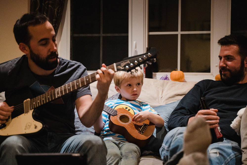 A little boy plays a ukelele with his dad and uncle.
