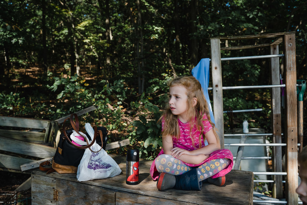 A little girl sits on a crate at Restoration Farm.