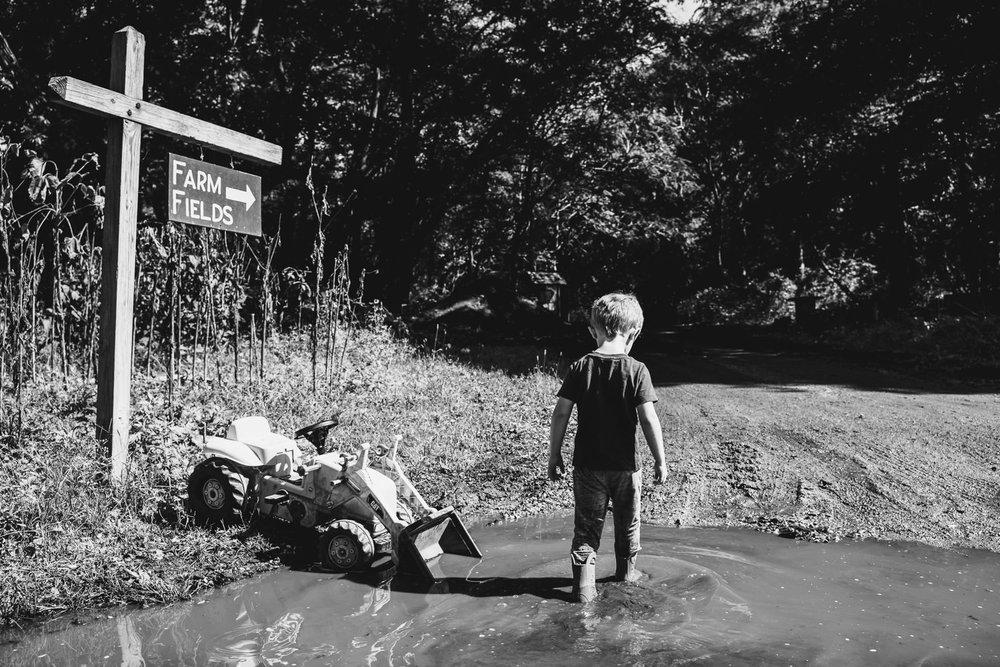 A little boy walks through a muddy puddle at Restoration Farm.
