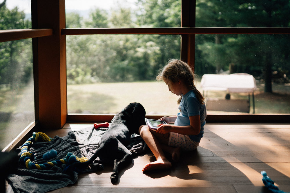 A little girl sits with her dog on a porch.