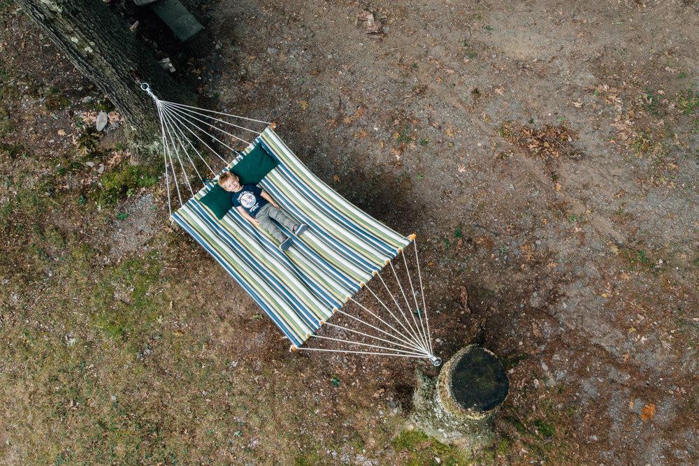 A little boy lies in a hammock.