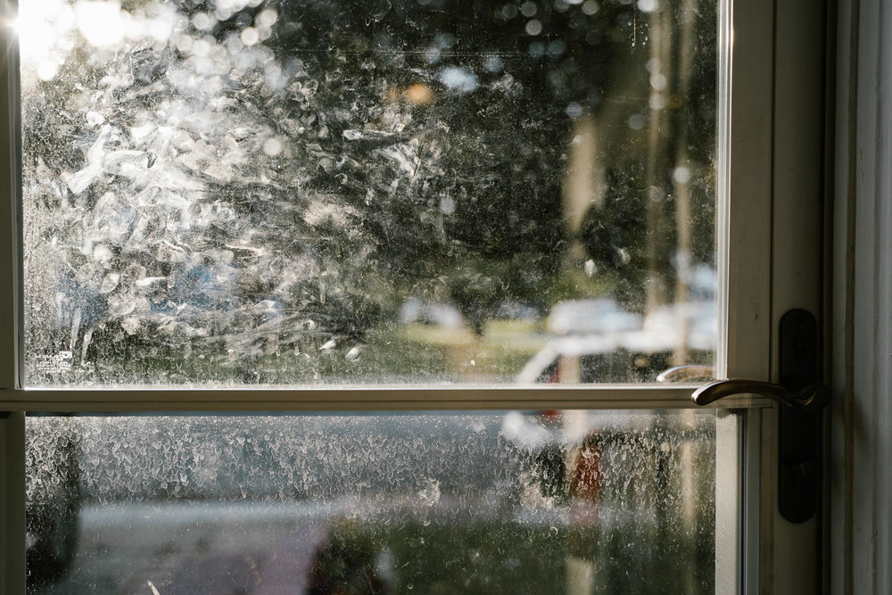 Fingerprints on a glass storm door.
